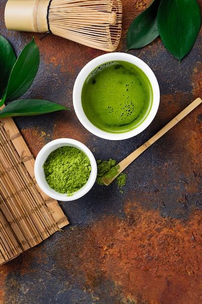 Grünes matcha teegetränk und teezubehör auf dunklem rostigem Premium Fotos