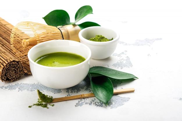 Grünes matcha teegetränk und teezubehör auf weißem hintergrund Premium Fotos