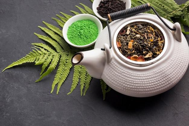 Grünes matchateepulver und trockenes kraut mit keramischer teekanne auf schwarzer oberfläche Kostenlose Fotos