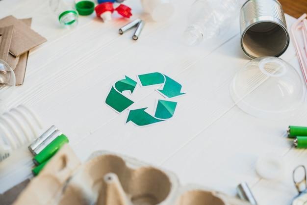 Grünes recycling-symbol umgeben mit abfallgegenständen Kostenlose Fotos
