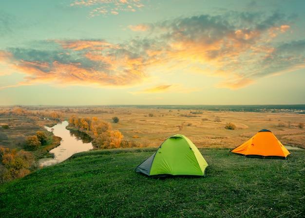 Grünes und orange zelt am flussufer am sonnigen sommertag Premium Fotos
