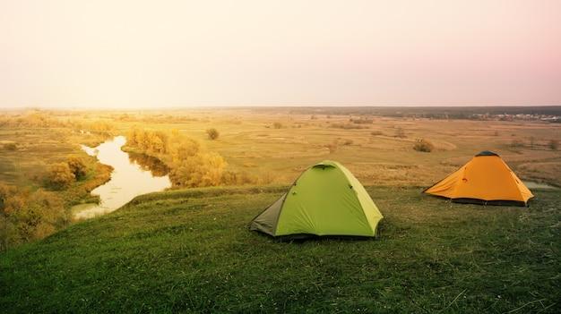 Grünes und orangefarbenes zelt am fluss Premium Fotos