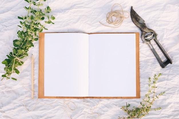 Grünpflanzezweige in der nähe von gartenschere, bleistift, thread und notizbuch Kostenlose Fotos