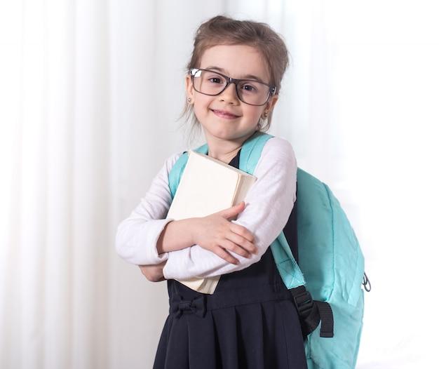 Grundschülerin mit rucksack und buch Kostenlose Fotos