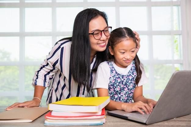 Grundschulemädchen, das computer mit lehrer studiert Premium Fotos