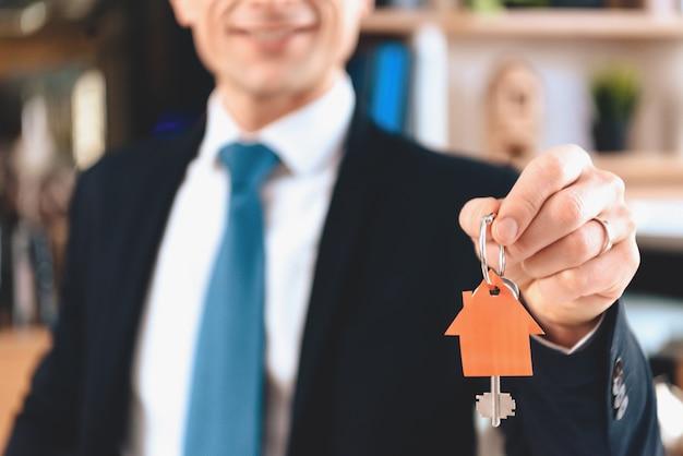 Grundstücksmakler zeigt schlüssel des neuen hauses. Premium Fotos