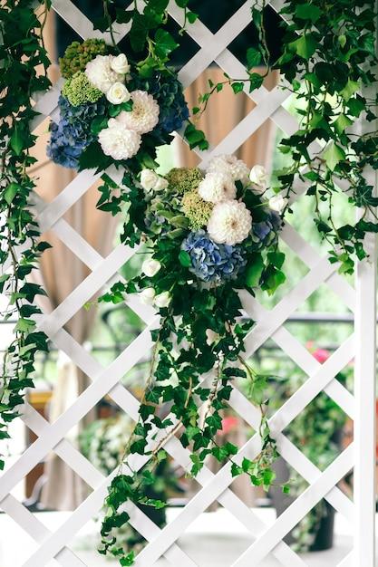 Grüne Girlanden mit weißen und blauen Blumen hängen an der Wand ...