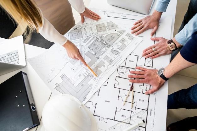 Gruppe architekten, die plan auf tabelle analysieren Kostenlose Fotos