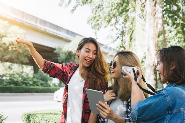 Gruppe asiatinnen, die kamera verwenden, um foto beim reisen am park in der städtischen stadt in bangkok zu machen Kostenlose Fotos