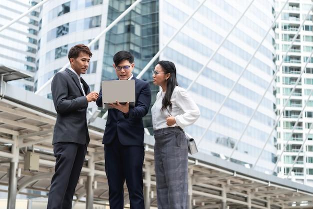 Gruppe asiatische geschäftsleute, die mit seinem reifen kollegen arbeiten und sich besprechen und einen laptop an im freien in der hauptstadt verwenden Premium Fotos