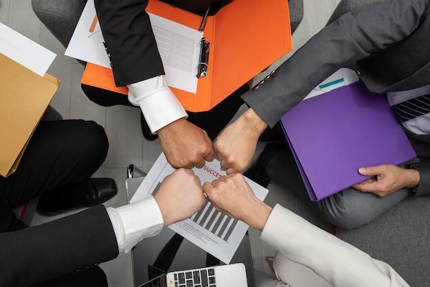 Gruppe asiatische geschäftsleute hände, die fauststoß machen, gestikulieren zusammen in der teamwork. Premium Fotos