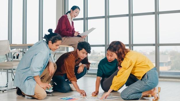 Gruppe asiatischer junger kreativer leute in der freizeitkleidung, die geschäfts-brainstorming-besprechungsideen diskutiert, die designplan des mobilen anwendungssoftwareentwurfs auf boden im büro angelegt werden. teamwork-konzept für mitarbeiter. Kostenlose Fotos