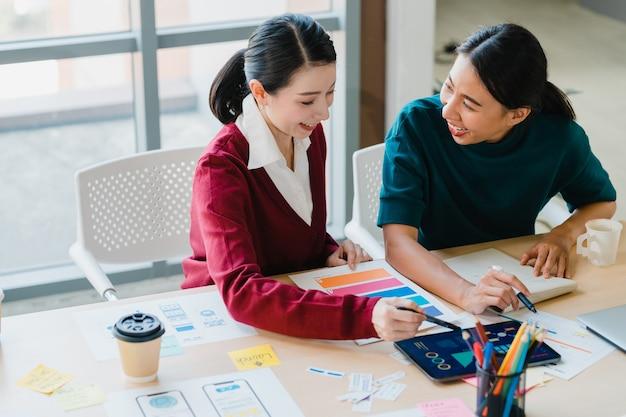 Gruppe asiatischer junger kreativer leute japanischer weiblicher chefaufseher, der praktikant oder neues mitarbeiter hispanisches mädchen unterrichtet, das bei der schwierigen aufgabe im modernen büro hilft. teamwork-konzept für mitarbeiter. Kostenlose Fotos