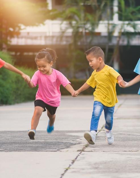 Gruppe asiatisches kinderhändchenhalten und auf gehweg in der schule zusammen laufen oder gehen Premium Fotos