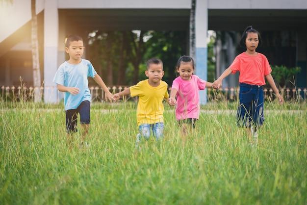 Gruppe asiatisches kinderhändchenhalten und auf rasenfläche in der schule zusammen laufen oder gehen Premium Fotos