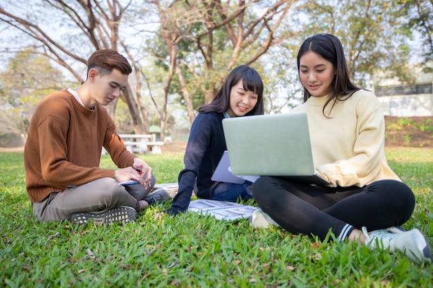 Gruppe asiatisches sitzen der hochschulstudenten auf dem grünen gras, das draußen in einem park zusammenarbeitet und liest Premium Fotos