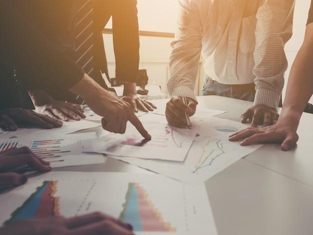 Gruppe der geschäftsmannsitzung analysieren die unternehmensleistung und das wachstum, die mit informationsdatenpapier unternehmen sind. Premium Fotos