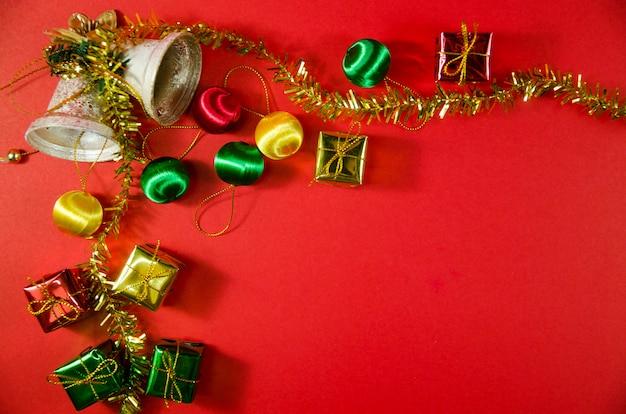 Gruppe der glocke, des balls und des geschenks im weihnachten auf rotem hintergrund auf draufsicht Premium Fotos
