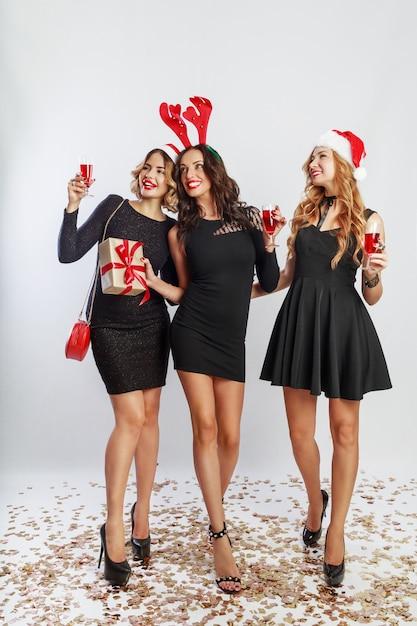Gruppe der glücklichen feierfrauen in den niedlichen neujahrsparty-maskeradenhüten, die große zeit zusammen verbringen. alkohol trinken, tanzen, spaß auf weißem hintergrund haben. volle länge. Kostenlose Fotos