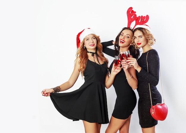 Gruppe der glücklichen feierfrauen in den niedlichen neujahrsparty-maskeradenhüten, die große zeit zusammen verbringen. alkohol trinken, tanzen, spaß auf weißem hintergrund haben. Kostenlose Fotos