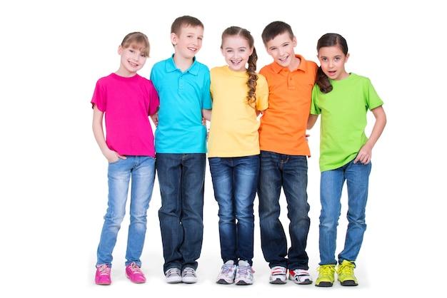 Gruppe der glücklichen kinder in den bunten t-shirts, die zusammen in voller länge auf weißem hintergrund stehen. Kostenlose Fotos