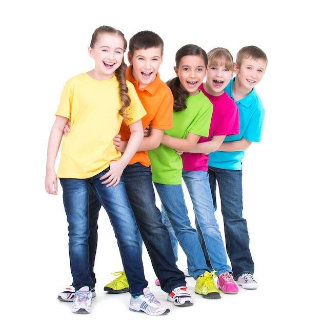 Gruppe der glücklichen kinder in den bunten t-shirts stehen hintereinander auf weißem hintergrund. Kostenlose Fotos