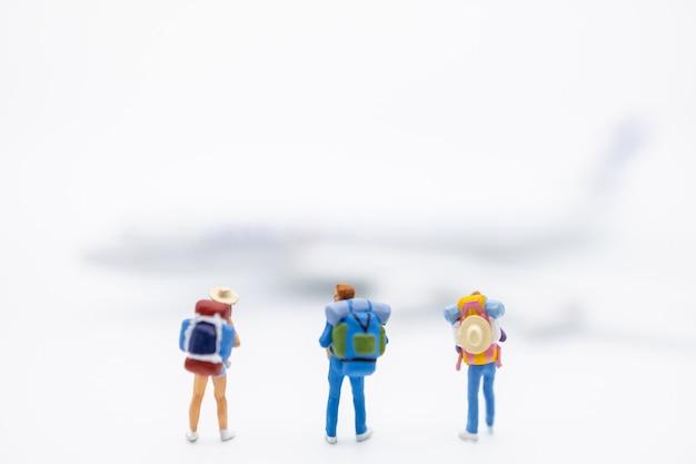Gruppe der reisendminiaturzahl mit dem rucksack, der auf weiß mit minispielzeugflugzeug steht. Premium Fotos