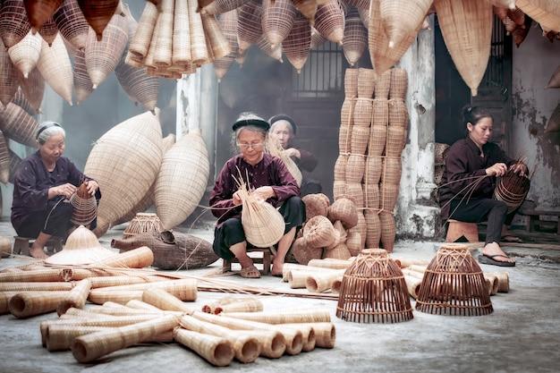 Gruppe des alten vietnamesischen weiblichen handwerkers, der die traditionelle bambusfischfalle macht oder am alten traditionellen haus in thu sy-handelsdorf, hung yen, vietnam, traditionelles künstlerkonzept spinnt Premium Fotos