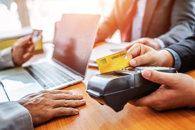 Gruppe des geschäfts kreditkarte mit nfc-zahlungssystem im modernen büro halten. Premium Fotos