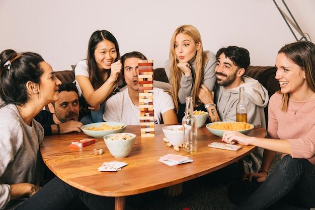 Gruppe des glücklichen spielenden tabletopspiels Kostenlose Fotos