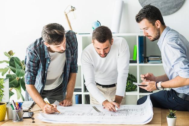 Gruppe des männlichen architekten plan analysierend Kostenlose Fotos