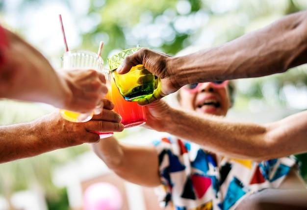 Gruppe des verschiedenen älteren erwachsenen, der zusammen getränk durch das pool genießt Kostenlose Fotos
