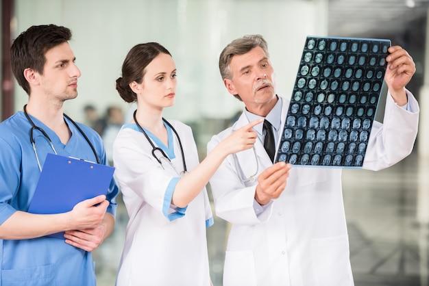 Gruppe doktoren, die röntgenstrahl am offie betrachten. Premium Fotos