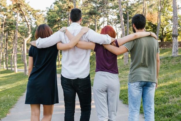 Gruppe erwachsene freunde, die entlang straße umarmen und gehen Kostenlose Fotos