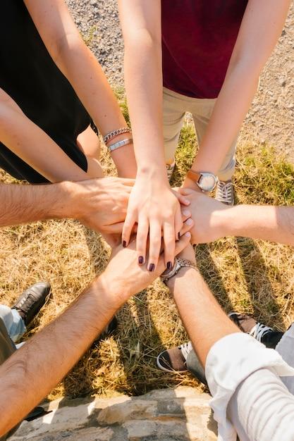 Gruppe erwachsene freunde, die hände stehen und zusammenfügen Kostenlose Fotos