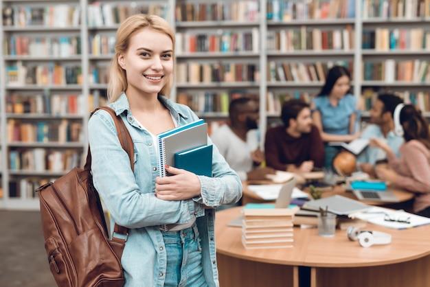 Gruppe ethnische multikulturelle studenten, die in der bibliothek sitzen. Premium Fotos