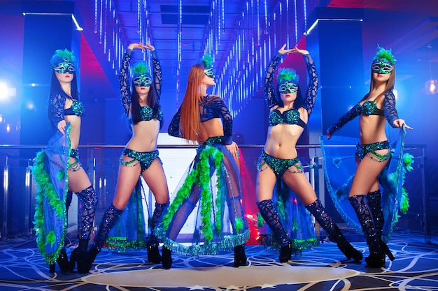 Gruppe exotischer tänzer, die bunte bühnenkarnevalsoutfits tragen Kostenlose Fotos