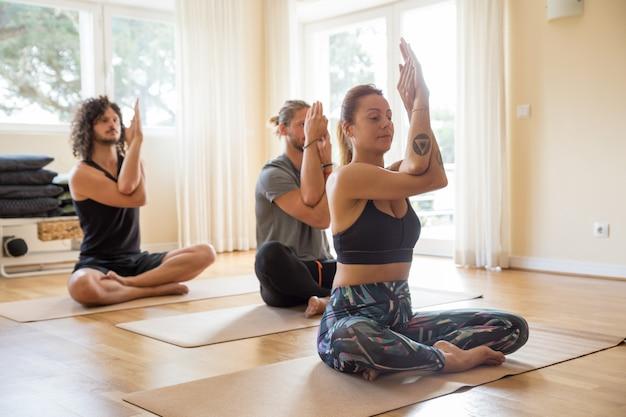Gruppe fokussierte yogis, die zuhause klasse genießen Kostenlose Fotos
