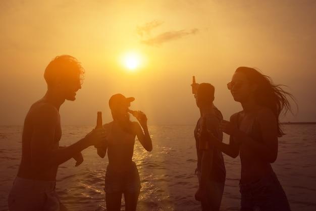 Gruppe freunde, die am strand im dämmerungssonnenuntergang feiern und trinken Premium Fotos