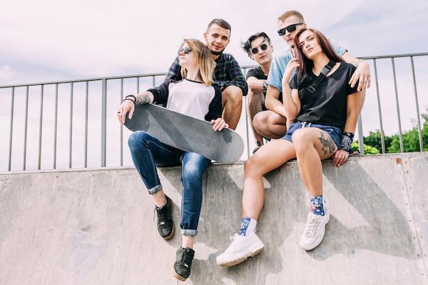 Gruppe freunde, die auf geländer mit skateboard sitzen Kostenlose Fotos