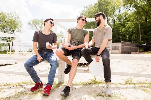 Gruppe freunde, die auf strandzaun plaudern Kostenlose Fotos