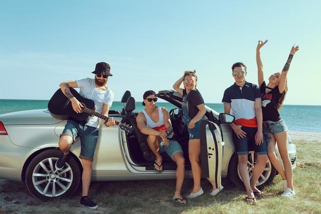 Gruppe freunde, die auto bereitstehen Premium Fotos