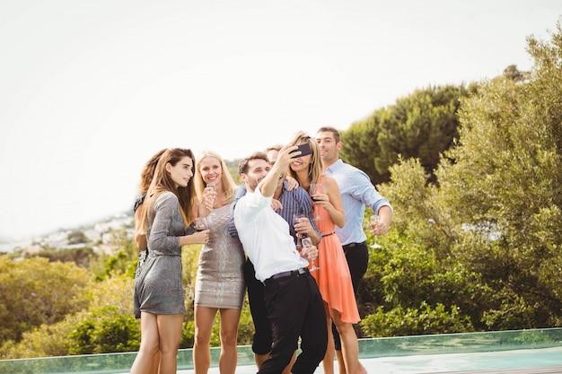 Gruppe freunde, die ein selfie nahe dem swimmingpool in einem erholungsort nehmen Premium Fotos