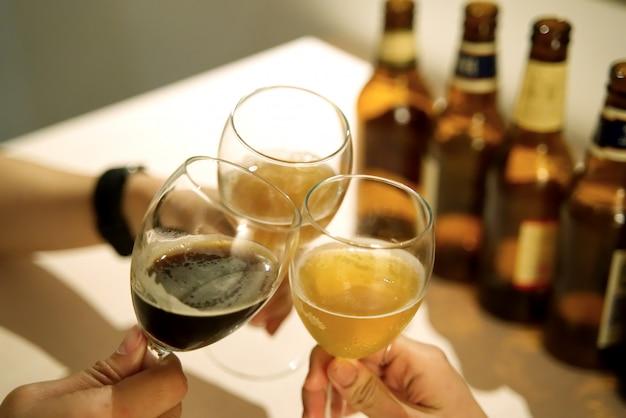 Gruppe freunde, die glas bier im raum rösten. Premium Fotos