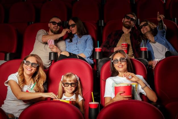 Gruppe freunde, die im kino mit popcorn und getränken sitzen Premium Fotos