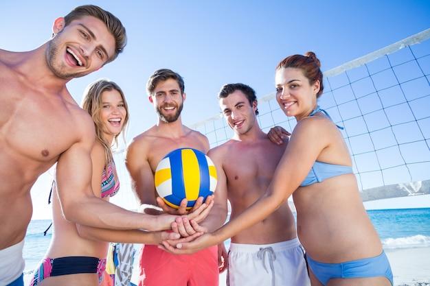 Gruppe freunde, die volleyball halten und an der kamera lächeln Premium Fotos