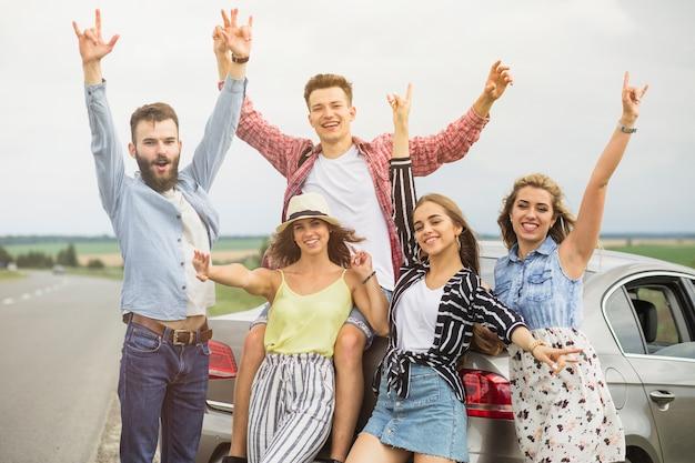 Gruppe freunde, die vor dem auto anhebt das handgestikulieren stehen Kostenlose Fotos