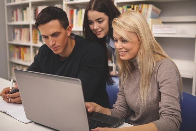 Gruppe freunde, die zusammen studieren an der bibliothek genießen Premium Fotos