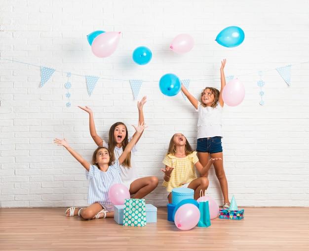 Gruppe freunde in einer geburtstagsfeier, die mit ballonen spielt Premium Fotos