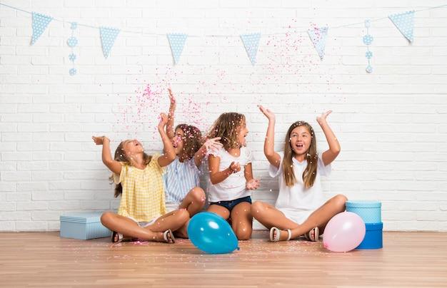 Gruppe freunde in einer geburtstagsfeier, die mit konfetti spielt Premium Fotos